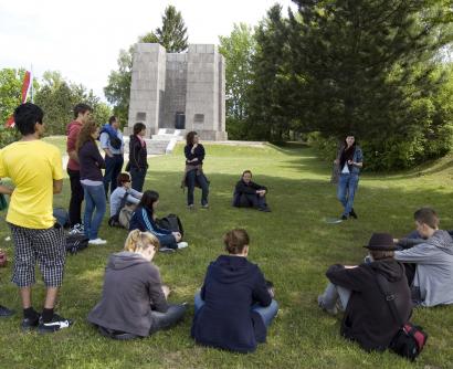 Jugendliche auf Wiese sitzend in der KZ-Gedenkstätte Mauthausen